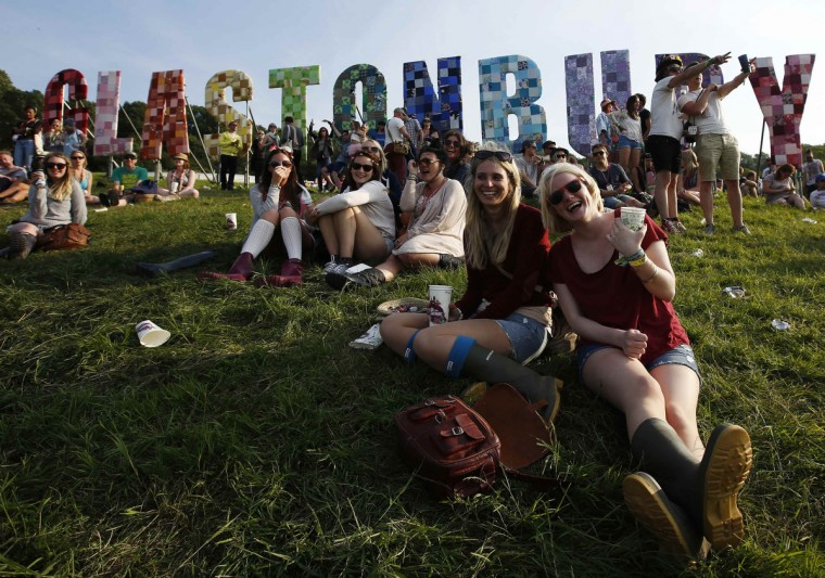 Festival goers watch their friends play rounders on the first day of Glastonbury music festival at Worthy Farm in Somerset, June 26, 2013. (Olivia Harris/Reuters)