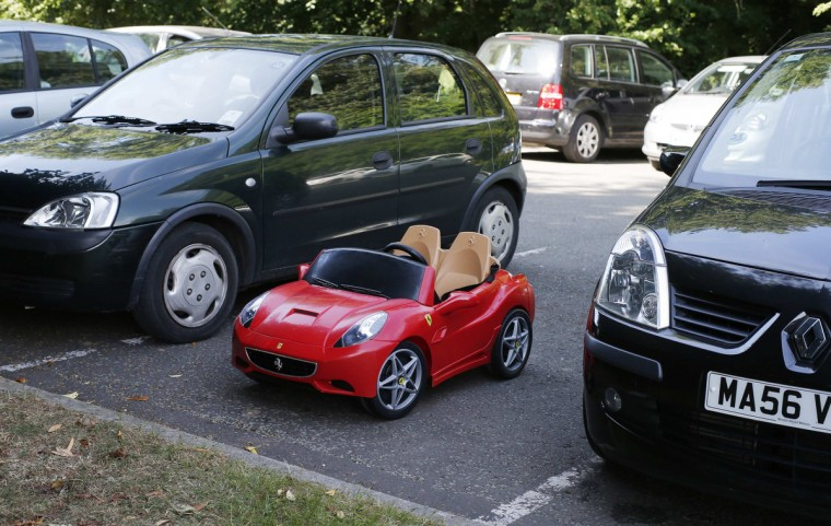 A child's toy Ferrari is parked between two hatchbacks at the Hale Barns Cricket Club in Altrincham, Cheshire, northern England. (Phil Noble/Reuters photo)
