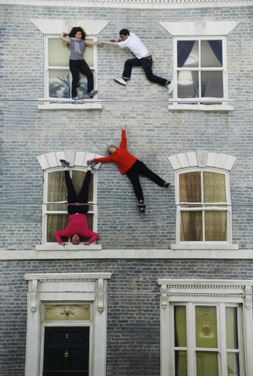 """Visitors are seen by their reflections as they pose on Argentine artist Leonado Erlich's optical illusion installation """"Dalston House"""" in east London June 25, 2013. (Luke MacGregor/Reuters)"""