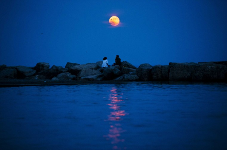 The moon is seen in an abnormally red colour as it rises in the Toronto Beaches. (Mark Blinch/Reuters photo)