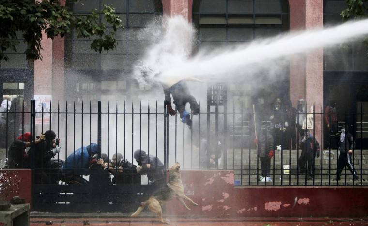 A student is hit by a jet of water sprayed by riot police during a protest against the government to demand changes in the public state education system, in Santiago. Chilean students have been protesting against what they say is profiteering in the state education system. (Carlos Vera/Reuters)