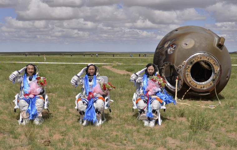 Astronauts (L-R) Zhang Xiaoguang, Nie Haisheng and Wang Yaping salute after returning to earth in the re-entry capsule of China's Shenzhou-10 spacecraft at its main landing site in north China's Inner Mongolia Autonomous Region. Three Chinese astronauts returned to Earth on Wednesday, touching down in north China's Inner Mongolia after a successful 15-day mission in which they docked with a manned space laboratory. (Reuters)