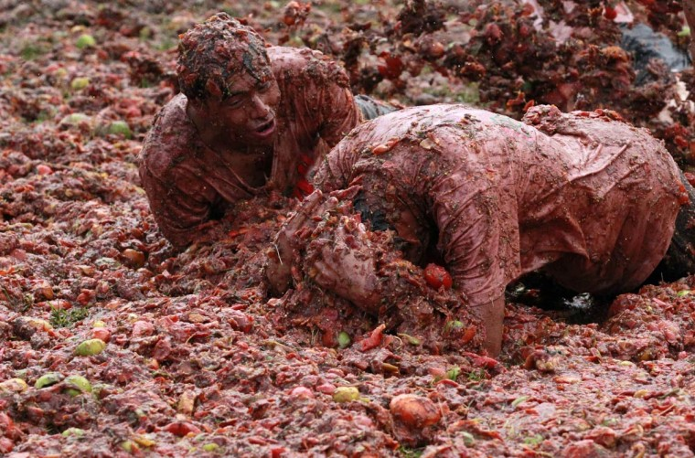 "Revellers play with tomato pulp during the annual ""Tomatina"" (tomato fight) in Sutamarchan province in Boyaca June 2, 2013. (John Vizcaino/Reuters)"