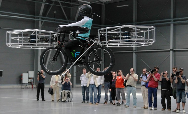 Journalists attend a presentation of a flying bicycle, carrying a dummy, at Letnany's fair hall in Prague. The flying bicycle, which was was created by Czech designers, is kept aloft by six electrically-powered propellers. (Petr Josek/Reuters photo)