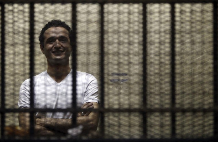 Egyptian activist Ahmed Douma stands behind bars during his trial at the New Cairo court, on the outskirts of Cairo June 3, 2013. A court sentenced Douma to six months in prison on Sunday, with the option of paying a bail of 5,000 Egyptian pounds ($716) to be released. Douma was accused of insulting President Mohamed Mursi and spreading false information with the purpose of disrupting public order.(Amr Abdallah Dalsh/Reuters)