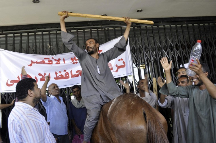 Protesters chant slogans in front of Luxor governorate building to protest against the newly-appointed governor, Adel Mohamed al-Khayat, who was a member of the militant group, al-Gamaa al-Islamiya, in Luxor. (stringer/Reuters photo)