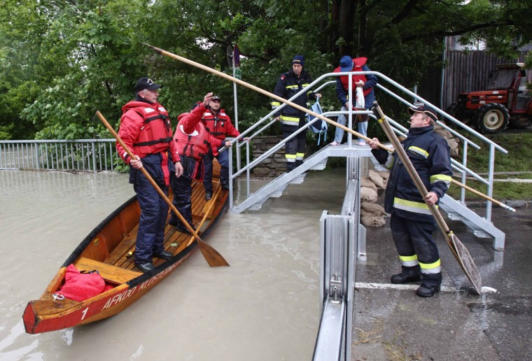 A fireman passes a spike to his colleague over a barrier holding back the flood water of the swollen Danube river in Klosterneuburg, the neighboring city north of Vienna, June 4, 2013. Torrential rain in Tyrol, Salzburg, Upper and Lower Austria caused heavy flooding over the weekend, forcing people to evacuate their homes. (Heinz-Peter Bader/Reuters)