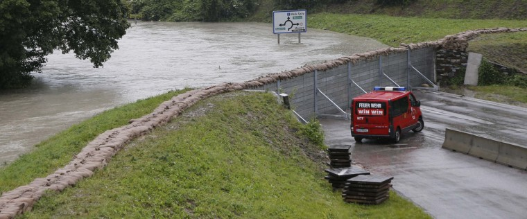 Members of the emergency services drive next to a barrier to protect from flooded river Danube in the village of Stein-Krems in Lower Austria, about 80 km (50 miles) west of Vienna June 4, 2013. Torrential rain in Salzburg, Upper and Lower Austria caused heavy flooding over the past days, forcing people to evacuate their homes. (Leonhard Foeger/Reuters)