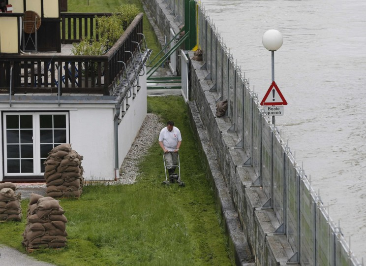 A resident mows the lawn in village of Stein-Krems next to the flooded river Danube in Lower Austria, about 80 km (50 miles) west of Vienna June 5, 2013. Torrential rain in Salzburg, Upper and Lower Austria caused heavy flooding over the past days, forcing people to evacuate their homes. (Leonhard Foeger/Reuters)