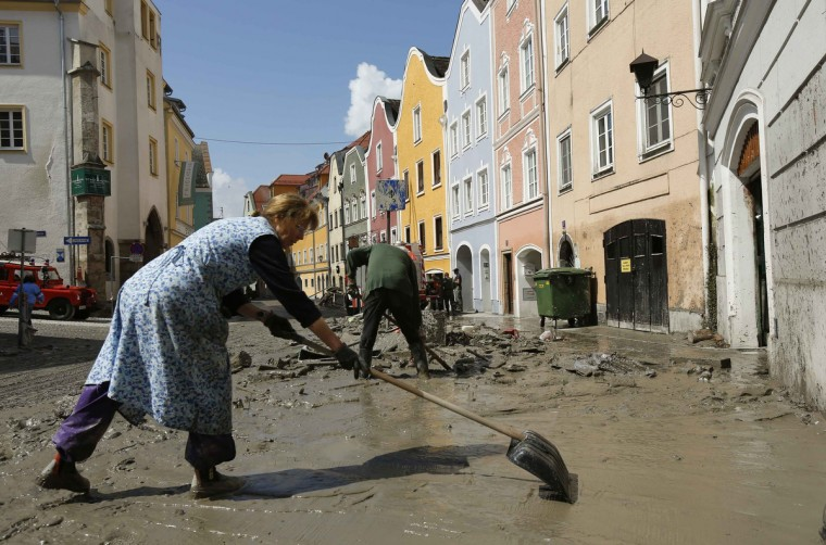 A resident cleans mud from the footpath in front of her house following flooding along the river Inn in the Austria-German border town of Schaerding June 5, 2013. Chancellor Angela Merkel promised 100 million euros to victims of Germany's worst flood in a decade on Tuesday as she toured areas devastated by the deluge, which has killed 12 people across central Europe. (Wolfgang Rattay/Reuters)