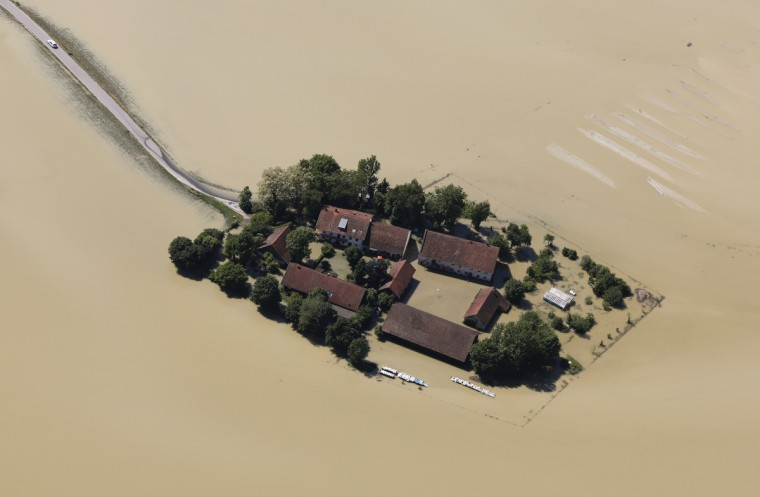 A car leaves a small settlement surrounded by the floods of the river Danube near the eastern Bavarian city of Deggendorf June 5, 2013. Chancellor Angela Merkel promised 100 million euros to victims of Germany's worst flood in a decade on Tuesday as she toured areas devastated by the deluge, which has killed 12 people across central Europe. (Wolfgang Rattay/Reuters)