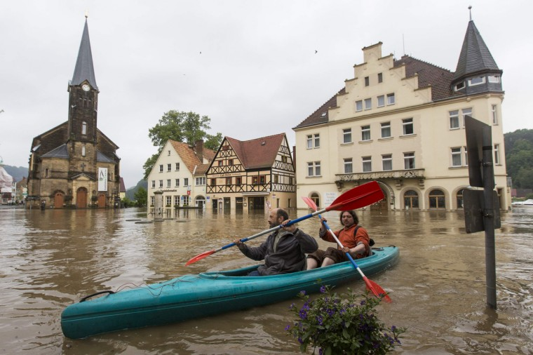 Two men paddle across a flooded market square after the Elbe river broke its banks during a flood in the east German town of Wehlen in the federal state of Saxony June 4, 2013. (Thomas Peter/Reuters)