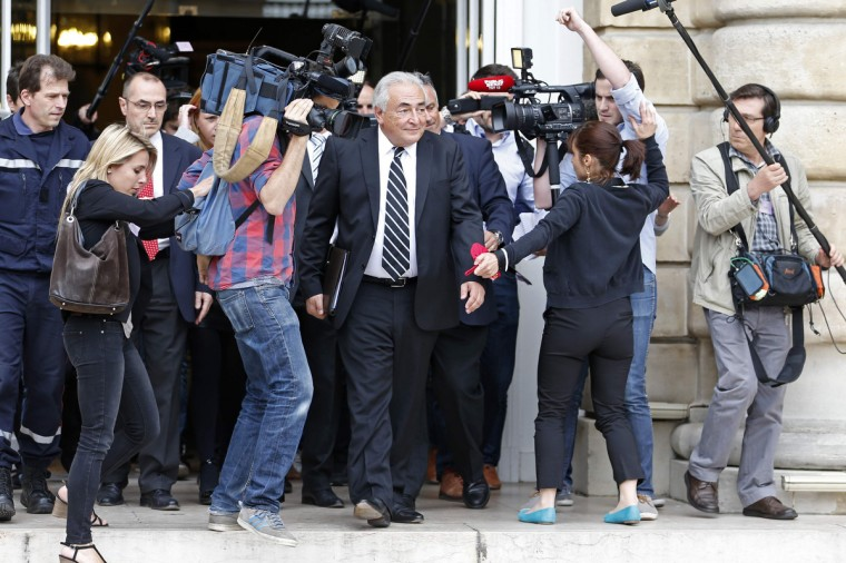 Former International Monetary Fund (IMF) chief Dominique Strauss-Kahn (C) is surrounded by journalists as he leaves after a French Senate commission inquiry on the role of banks in tax evasion in Paris. (Charles Platiau/Reuters)
