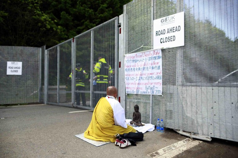 A Buddhist demonstrator protests at the security fence surrounding the G8 Summit at Lough Erne in Enniskillen, Northern Ireland June 17, 2013. (Cathal McNaughton/Reuters)