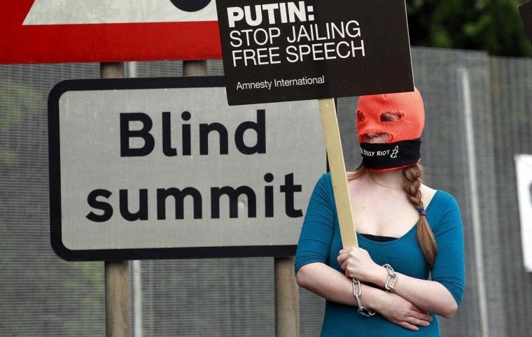 """A demonstrator wears a """"Free Pussy Riot"""" balaclava and holds a placard that reads """"Putin: Stop Jailing Free Press"""" as she protests at the security fence surrounding the G8 Summit at Lough Erne in Enniskillen, Northern Ireland June 17, 2013. (Cathal McNaughton/Reuters)"""