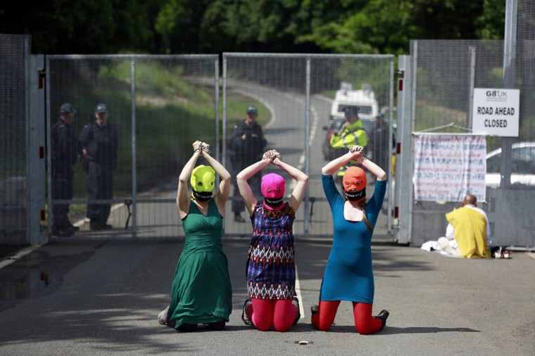"Demonstrators wear ""Free Pussy Riot"" balaclavas as they protest at the security fence surrounding the G8 Summit at Lough Erne in Enniskillen, Northern Ireland June 17, 2013. (Cathal McNaughton/Reuters)"