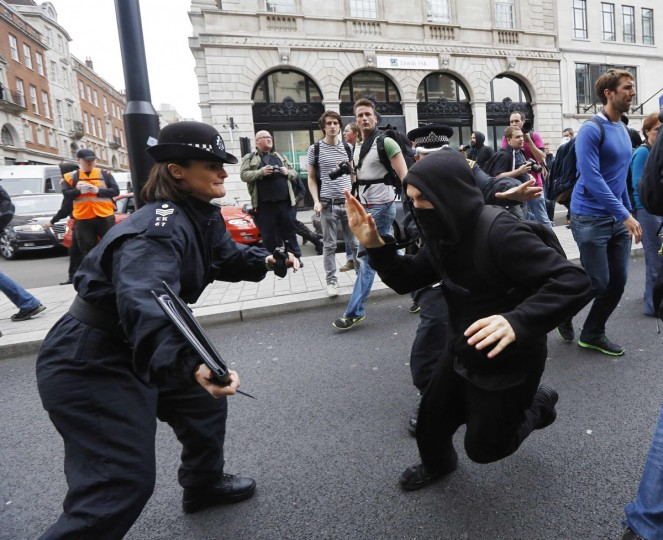 A protester demonstrating against the upcoming G8 summit tries to evade a police officer in central London. Police in riot gear moved in on a building in London's Soho district where activists had planned an anti-G8 protest through the British capital on Tuesday, before next week's summit of world leaders in Enniskillen, Northern Ireland. (Luke Macgregor/Reuters)