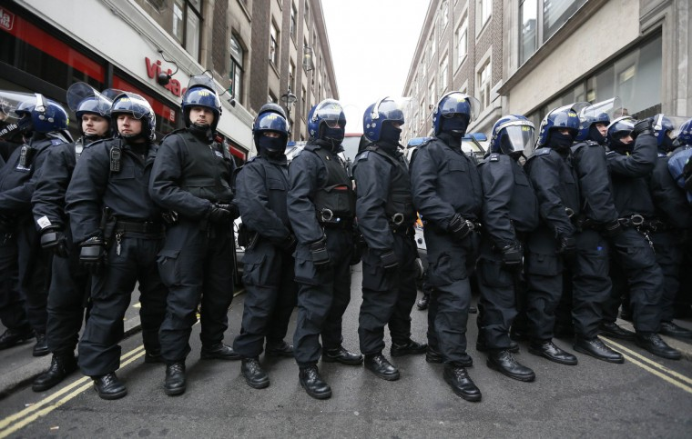 Police officers form a cordon after raiding a building used as a base for demonstrators protesting against the upcoming G8 summit in central London June 11, 2013. Police in riot gear moved in on a building in London's Soho district where activists had planned an anti-G8 protest through the British capital on Tuesday, before next week's summit of world leaders in Enniskillen, Northern Ireland. (Stefan Wermuth/Reuters)