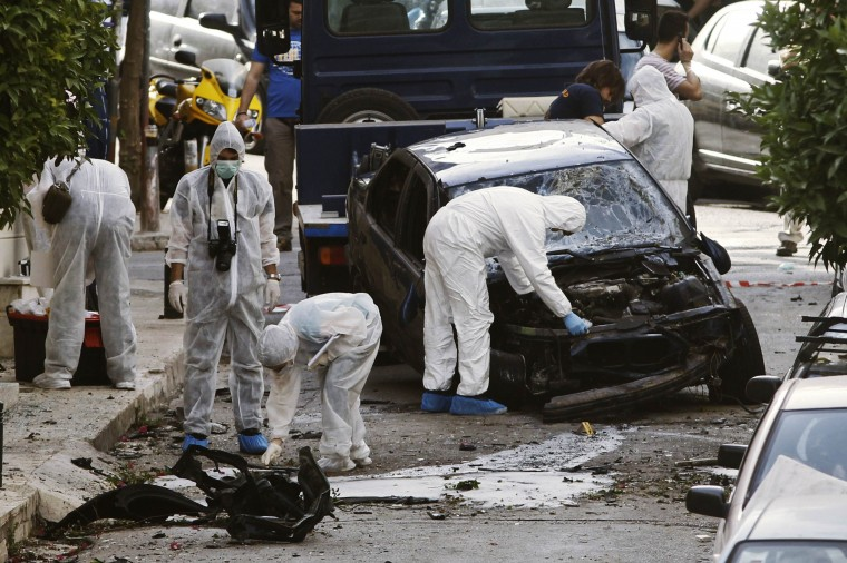 Police investigators search for evidence at the site of a bomb explosion in a suburb of Athens June 7, 2013. A time bomb exploded outside the Athens home of a Greek prison director overnight on Friday, smashing windows and slightly injuring one woman in the face, police officials said. (Yorgos Karahalis/Reuters)