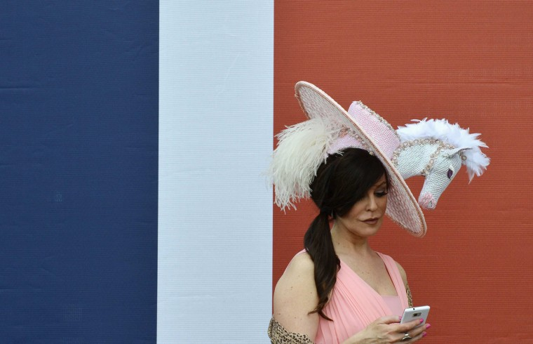 A racegoer wearing an equine themed hat checks her phone on the first day of the Royal Ascot horse racing festival at Ascot in southern England. (Toby Melville/Reuters photo)