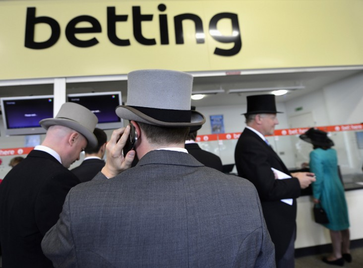 Racegoers queue to place bets during the first day of the Royal Ascot horse racing festival at Ascot in southern England. (Toby Melville/Reuters photo)