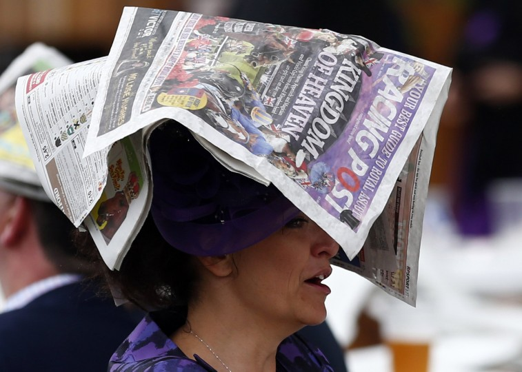 A woman uses a newspaper to protect her hat from the rain during the first day of the Royal Ascot horse racing festival at Ascot, southern England. (Darren Staples/Reuters photo