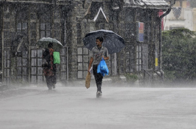 People hold umbrellas as they walk in a heavy rain shower in the northern Indian hill town of Shimla. India's monsoon rains recorded higher than average levels in the first week of the four-month rainy season, weather office sources told Reuters on Thursday, reflecting a timely onset and progress so far over southern states. (Stringer/Reuters photo)
