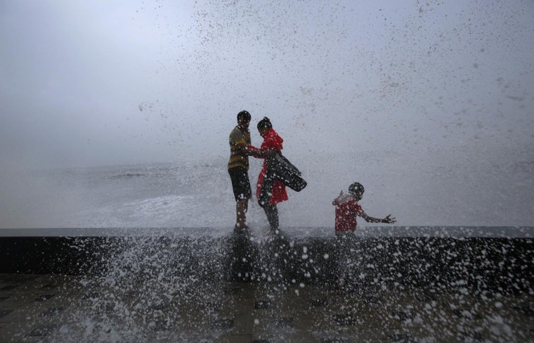 A man and woman embrace as waves crash over a sea wall as it rains during India's monsoon season in Mumbai, June 13, 2013. India's monsoon recorded higher than average levels for the second straight week, weather office data showed, aiding the rains to cover half of the country two days ahead of schedule. (Vivek Prakash/Reuters)