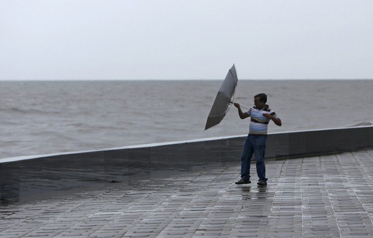 A man struggles with an upturned umbrellas as gusts of wind blow during monsoon season in Mumbai. (Vivek Prakash/Reuters)