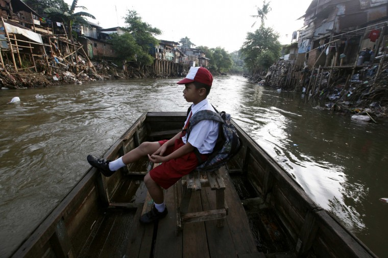 A boy sits in a wooden boat transporting him across a river to go to school in Jakarta. Local residents say that they are highly dependent on the river due to their lack of shower, washing and toilet facilities. World Environment Day is celebrated annually on June 5. (Enny Nuraheni/Reuters)