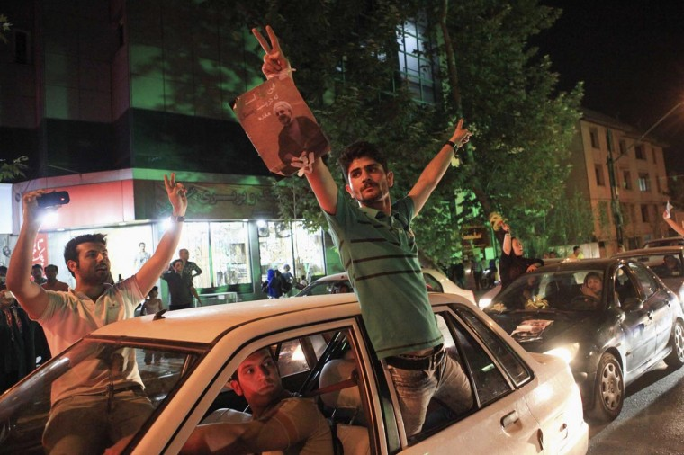 Supporters of moderate cleric Hassan Rohani gesture as they celebrate his victory in Iran's presidential election along a street in Tehran June 15, 2013. (Yalda Moayeri/Reuters)