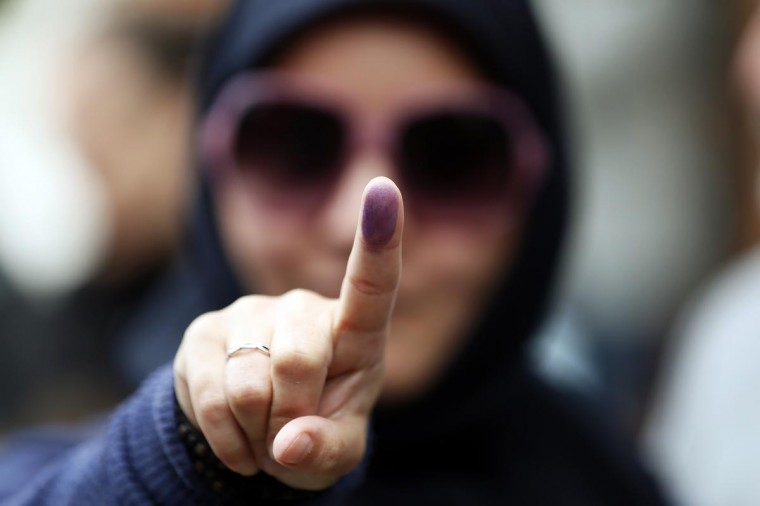 A woman shows the ink stain on her finger, to prove that she has voted, outside the Iranian consulate in central London June 14, 2013. (Stefan Wermuth/Reuters)