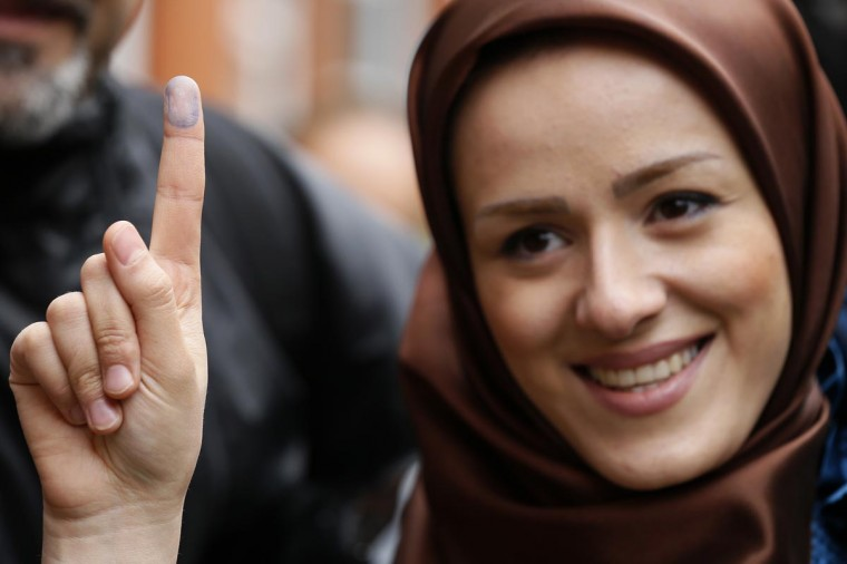 Voter Zeynab shows the ink stain on her finger, to prove that she has voted, outside the Iranian consulate in central London June 14, 2013. The building was the focus for demonstrators, as it was used as a venue for British based Iranians to cast their vote in their country's election to choose a new president. (Stefan Wermuth/Reuters)