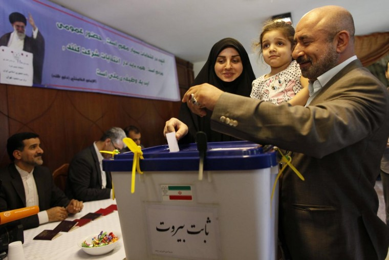 A woman casts her ballot with her family at a polling station at the Iranian embassy in Beirut June 14, 2013. (Jamal Saidi/Reuters)