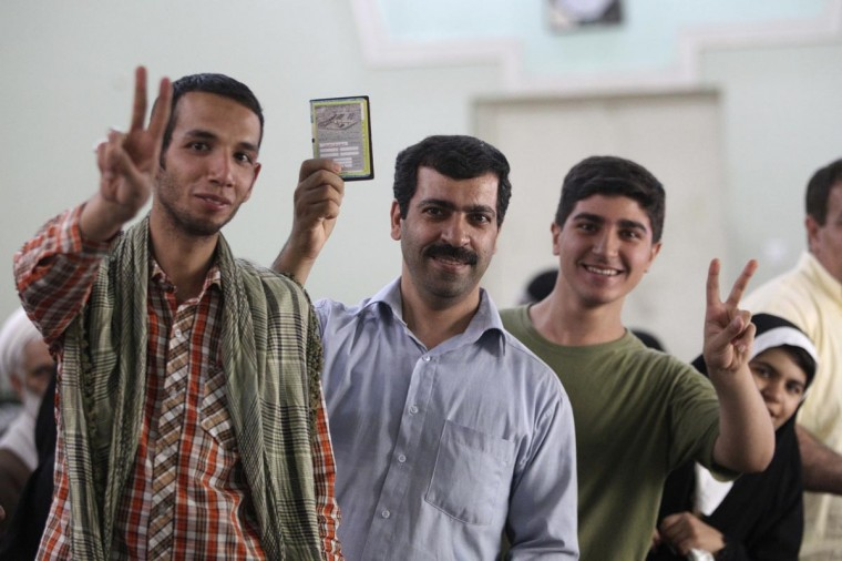 Iranians pose for pictures as they wait to vote during the Iranian presidential election at a Shi'ite mosque in Baghdad's Kadhimiya district, June 14, 2013. (Thaier al-Sudani/Reuters)