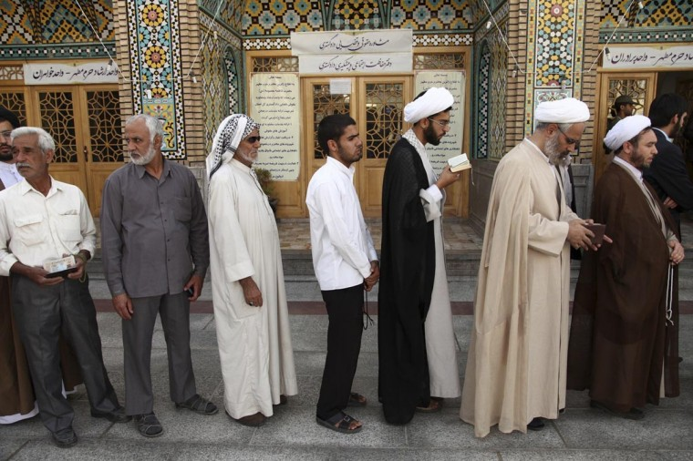 Men stand in line to vote during the Iranian presidential election at a mosque in Qom June 14, 2013. (Mohammad Akhlagi/Fars News via Reuters)