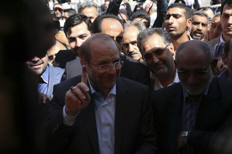 Presidential candidate Mohammad Baqer Qalibaf (front L) shows the ink on his finger after casting his ballot during the Iranian presidential election in Tehran June 14, 2013. (Sina Shiri/Fars News via Reuters)