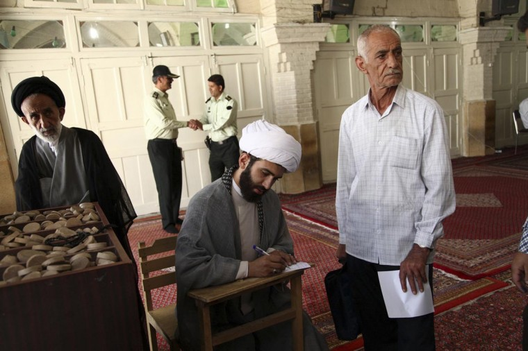 A cleric fills in his ballot paper during the Iranian presidential election at a mosque in Qom June 14, 2013. (Mohammad Akhlagi via Reuters)