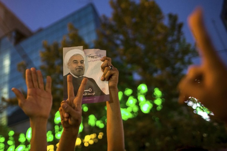 Supporters of moderate cleric Hassan Rohani hold a picture of him as they celebrate his victory in Iran's presidential election on a pedestrian bridge in Tehran June 15, 2013. (Sina Shiri/Fars News via Reuters)
