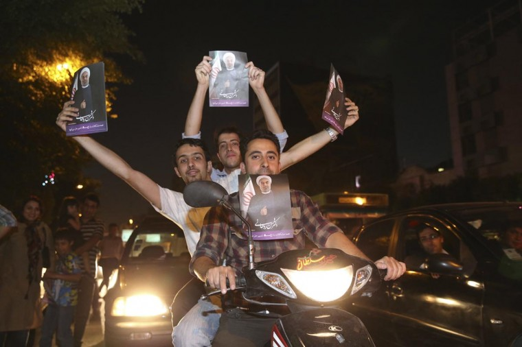 Supporters of moderate cleric Hassan Rohani hold his pictures as they celebrate his victory in Iran's presidential election on the streets of Tehran June 15, 2013. (Amir Hashen Dehgani/Fars News via Reuters)