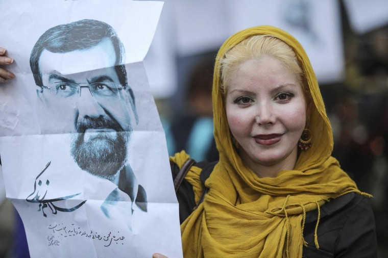 A supporter shows a campaign poster for Iranian presidential candidate Mohsen Rezaie on the streets of Tehran June 12, 2013. (Mehdi Ghassemi/Reuters)