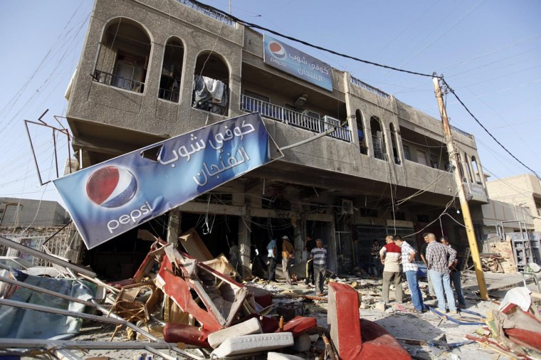 Residents gather at the premises of a coffee shop that was destroyed in a suicide bomb attack the night before, in Baghdad June 17, 2013. Five people were killed and 20 were wounded in the attack, police said. (Saad Shalash/Reuters)