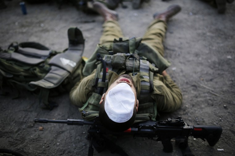 An Israeli soldier of the paratrooper brigade covers his face with a kippah, or skullcap, as he takes a break during a march near Jerusalem, marking the completion of their advanced training, at the end of which they receive their red paratrooper beret. (Amir Cohen/Reuters photo)