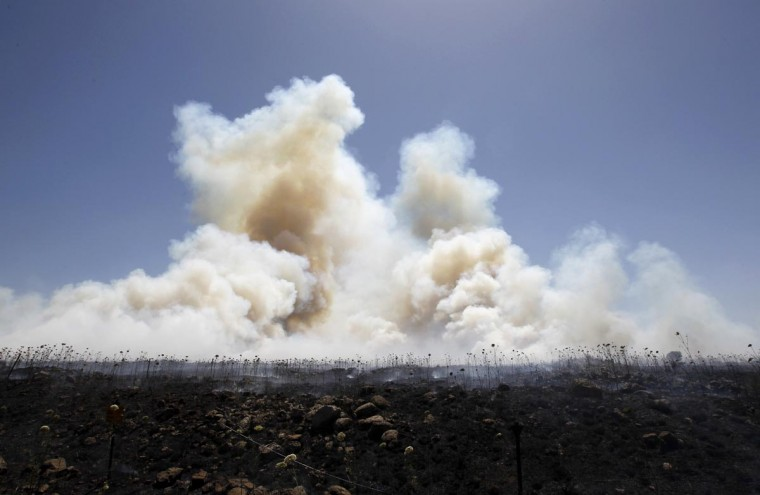 Smoke from brush fires set off by stray mortar bombs fired during fighting between forces loyal to the Syrian regime and rebels opposed to Syrian President Bashar al-Assad is seen near the Quneitra border crossing between Israel and Syria, in the Israeli-occupied Golan Heights, June 7, 2013. (Ammar Awad/Reuters)