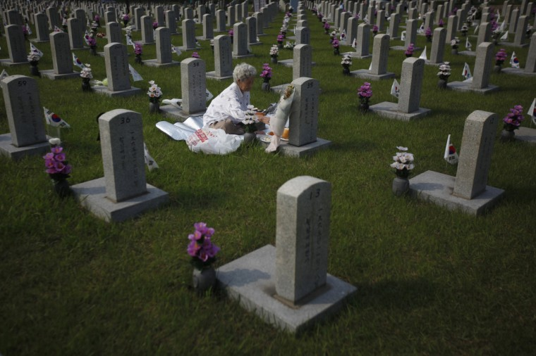 A woman pays her respects in front of the gravestone of her son who died for the country, at the national cemetery in Seoul on the eve of South Korea's Memorial Day to commemorate fallen patriots. (Kim Hong-Ji/Reuters)