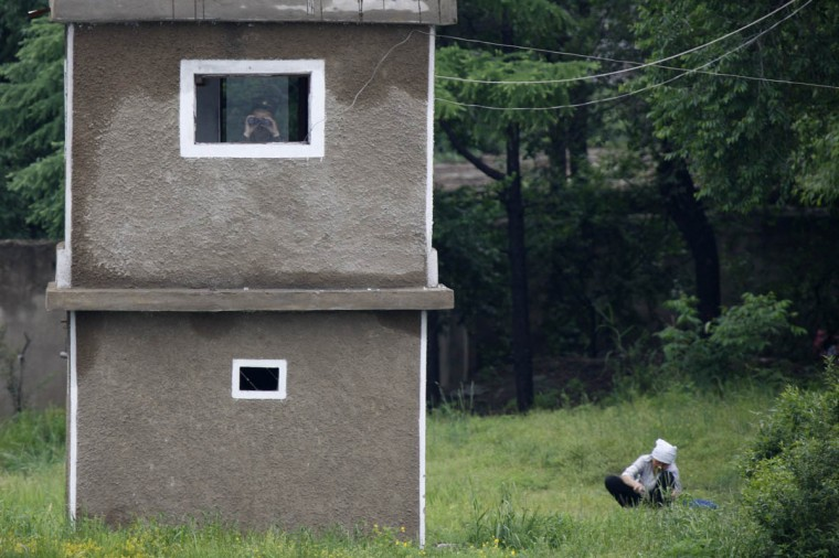 A North Korean soldier uses binoculars inside a guard tower as a woman works on a grassland on the banks of Yalu River, near the North Korean town of Sinuiju, opposite the Chinese border city of Dandong. Planned high-level talks between South and North Korean after a six-year hiatus and threats of war were scrapped on Tuesday, South Korean government officials said, over a seemingly minor disagreement over the diplomatic ranks of chief delegates. (Jacky Chen /Reuters photo)