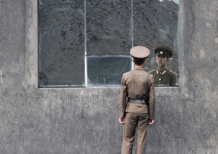 A North Korean soldier stands in front of a window along the banks of Yalu River near the North Korean town of Sinuiju, opposite the Chinese border city of Dandong, June 24, 2013. (Jacky Chen/Reuters)