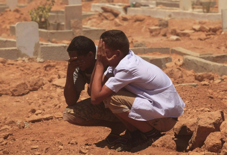 Men grieve over a grave at the funerals for those killed in Saturday's clashes at the Libya Shield brigade headquarters, in Benghazi June 9, 2013. (Esam Al-Fetori/Reuters)