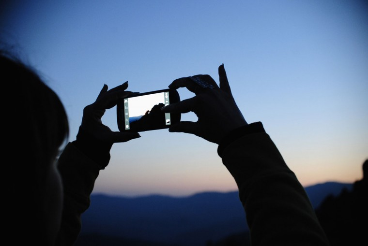 A girl takes photos of the Kokino megalithic observatory during the summer solstice celebration in Kumanovo, Macedonia. (Ognen Teofilovski/Reuters)