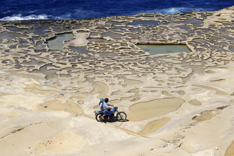 A man and his passenger ride a motorcycle near salt pans, believed to have been used for harvesting sea salt since Roman times, outside the village of Marsalforn, on the northern coast of the Maltese island of Gozo. (Darrin Zammit Lupi/Reuters photo)